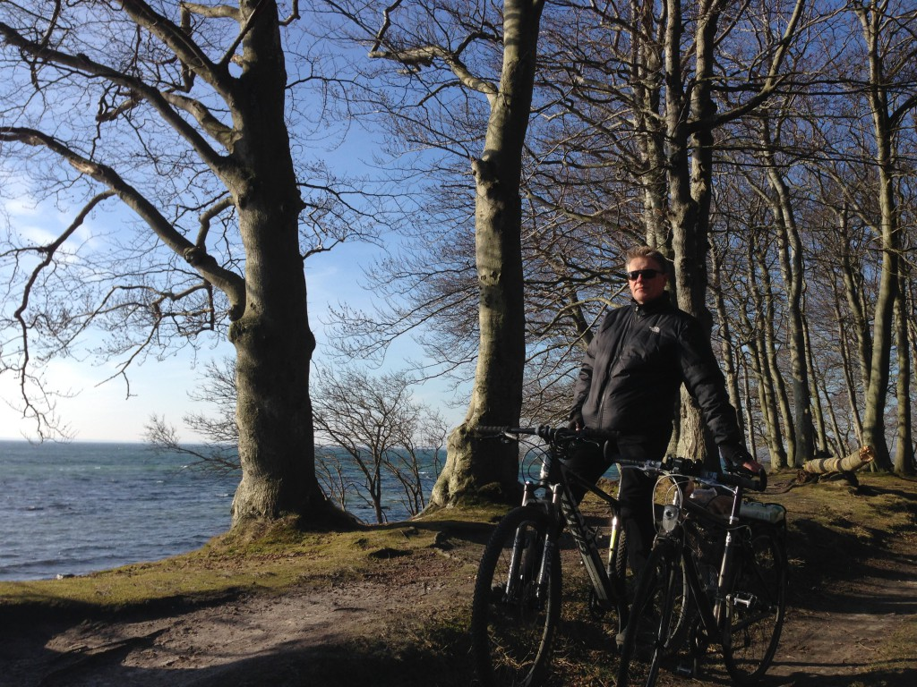 Per i skarp forårssol på cykel med morgenbrød fra Faxe Ladeplads på vej gennem skoven til Vemmetofte