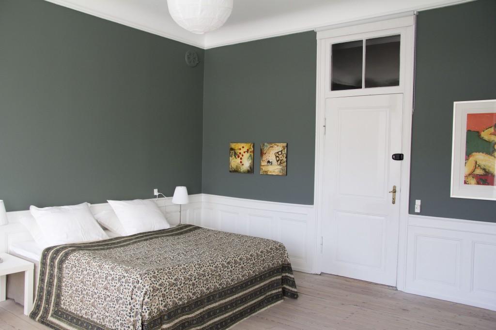 Rytterværelset er grønt med høje træpaneler og kunst på væggene. Sengene kan, som på de andre værelser, stilles som I ønsker.
